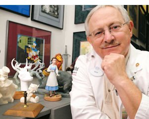 Art: S/R Laboratories Director Ron Stark poses along with maquettes - character models animators use to assist in their drawing - at his company's offices.