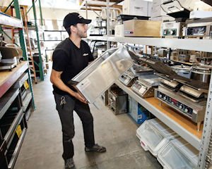 Labor: Co-owner Eddie Torossian places a refurbished piece of kitchen equipment on a shelf at Toro Kitchen supply in Canoga Park.