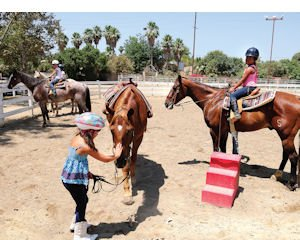 Train: Children learn to ride at summer camp at the Los Angeles Equestrian Center.