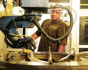 Metal: Klune Industries employee using a laser cutting tool.