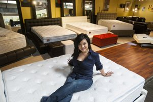 Tawny Lam, Nova Lifestyle Inc. president, with mattresses on display at company's Commerce showroom.