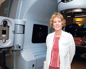 Health: Nancy Ellerbroek poses with a Linear Accelerator Treatment Machine at Holy Cross Cancer Center.