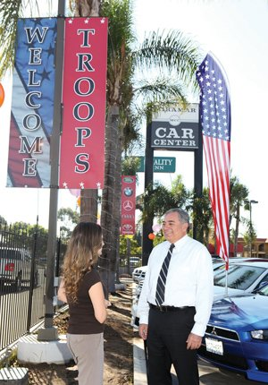 """Art Molina, who runs Miramar Car Center, talks with a customer outside of his dealership where the """"Welcome Troops"""" banners are prominently displayed. Molina estimates that one-third of his business comes from military personnel."""