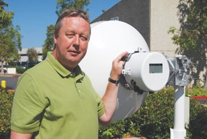 Photo courtesy of LightPointe Communications Inc. LightPointe CEO Heinz A. Willebrand shows off a LightPointe 80 gigahertz point-to-point radio. These radios are used by carriers and enterprises for long-distance connectivity between towers or buildings. It can transmit over 200 times faster than the typical broadband connection serving a home or business.