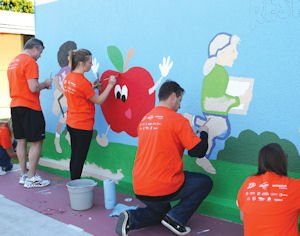 School-improvement team: Anaheim Ducks assistant coaches Bob Woods (far left) and Brad Lauer (second from right) work with Ducks staff members on mural at Mattie Lou Maxwell Elementary School