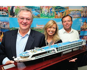 Cruisin': From left, Rudi Schreiner, Kristin Karst and Gary Murphy of Ama Waterways hold model of first ship company built.