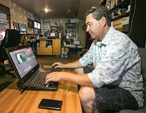 Casual Day: Freelance video editor David Dobson works on his laptop at his Burbank home office.