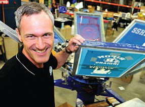 In Charge: Bolander holds silk screen featuring school logo and colors.