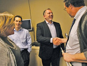 Burns: new Press-Enterprise publisher (second from right), with Freedom Chief Executive Aaron Kushner (second from left)