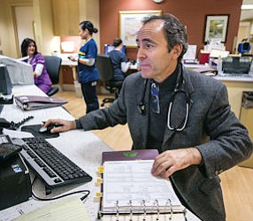 At Work: Pulmonologist Steven Taback checks lab results at Providence St. Joseph Medical Center in Burbank..