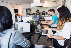 Working Twitter: Kris Sanchez, center, with staff at the Studio City house that serves as the headquarters of UberFacts.