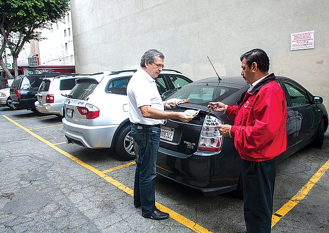 Price to Pay: Customer pays cash to a parking attendant at one of L&R Group's lots in downtown Los Angeles.
