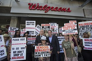 Pushing Back: Keith, left, and Brandon Marz with hired protesters in front of Walgreens in Hollywood.