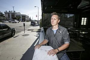 Chad Henderson, general manager at Local Peasant bar, surveys empty sidewalk.