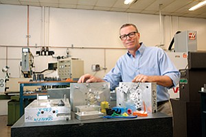 Operations Manager Martin Quinn stands behind examples of the complex tools and parts manufactured at Custom Engineering Plastics.
