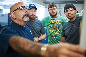 From left, instructor Randall Uerkvitz demonstrates how to operate machinery to veterans Scott Leoncini, Matthew Brown, Alexander Perez, participants in the Workshops for Warriors program.
