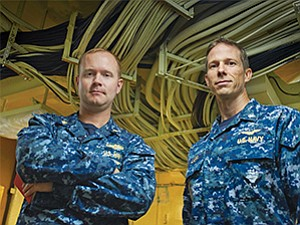 Cables for the USS Carl Vinson's new CANES computer network snake above the heads of Lt. Cmdr. Clifton Jackson, left, and Cmdr. Brent Lapp. Jackson is on the Vinson's information technology staff. Lapp is assistant program manager for the CANES program in San Diego.