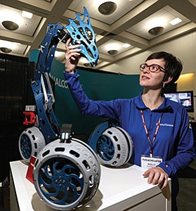 Molly Nicholas, a research and development engineer with Qualcomm Inc., shows off the company's Big Dragon Rover at the RoboUniverse Conference and Expo.