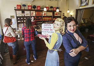 Gabriela Hernandez at Besame Cosmetics' Burbank shop with a sign that points to the firm's vintage style.