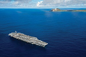 The aircraft carrier USS Ronald Reagan pauses off Iwo To, formerly known as Iwo Jima, in September to remember the pivotal World War II battle and lives lost. The Defense Department has decided that the next aircraft to operate off aircraft carriers will be an unmanned refueling tanker, rather than an unmanned strike aircraft. Photo courtesy of U.S. Navy