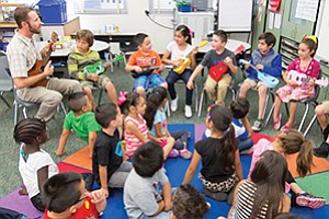 First-grade students at Normal Heights Elementary School in the San Diego Unified School District are learning how to play a ukulele as part of the Guitars in the Classroom curriculum.