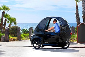 Virtue Cycles in San Diego makes a velomobile, an electric bike surrounded by an enclosure that resembles a very thin car.