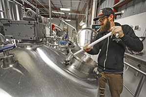 Tim Kamolz, product manager at Modern Times Beer, stirs a batch of the brew.