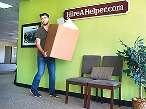 Zach Mennell carries a box as HireAHelper.com moves to new office space in Oceanside. The company is a small but growing player in San Diego County's $12.2 billion software industry.