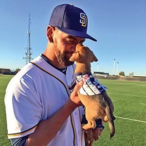 San Diego Padres starting pitcher Tyson Ross cuddles an adoptable pup from the Helen Woodward Animal Center at a recent game. Photo courtesy of Helen Woodward Animal Center