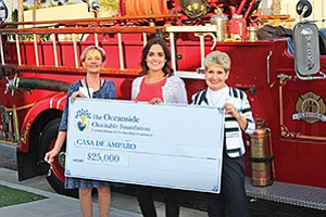 Oceanside Charitable Foundation founding member Suzy Martinek (left) and OCF Board Chair Beverly Holtz (right) present grant check to Shay Gebler with Casa de Amparo. Photo courtesy of Oceanside Charitable Foundation