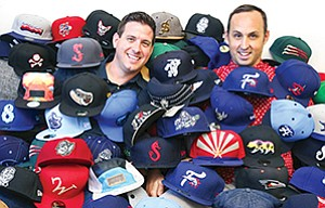 Jason Klein, left, and Casey White put on their creative thinking caps to come up with various names, logos and other branding efforts to pump up fan involvement for sports teams. The promotional efforts play a key part in drawing fans to minor league games.
