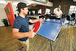 Power Digital Marketing employees Bill Wilkinson, left, and Ryan Larkin play Ping-Pong at the office. With the Great Recession fading in the rear-view mirror, employers are having to offer more amenities to retain quality employees. Perks range from recreational activities at work to companywide vacations.