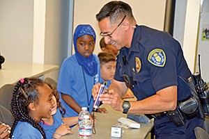 Officer Sam Morales shows Sofia Tesfarmarim how police dust for fingerprints, while Hoyam Mohamed watches. Photo courtesy of United Way of San Diego County