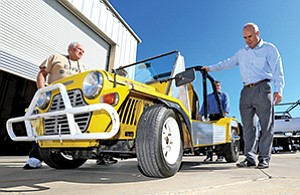 Volunteer mentors recently worked with students to install an electric drive system in this gasoline-powered vehicle, a British-designed Moke. The conversion was a project at the Electric & Networked Vehicle Institute at Coleman University. Shown are mentor Dan Wolfson (left), Coleman University administrator Rod Weiss, and mentor James Burns.