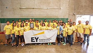 EY San Diego Office Managing Partner Robert Bruning (holding the plaque, left of center) and EY volunteers kick-off EY Connect Day, the firm's annual day of volunteerism, at Feeding America.Photo courtesy of Ernst & Young