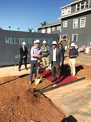 Icon Properties' owner AJ Tangsoc, in purple, and Reno Contracting founder and CEO Matt Reno shake hands on Nov. 17 at a ceremonial groundbreaking for 41 West, a luxury condo development in Banker's Hill. Photo courtesy of Reno Contracting Inc.