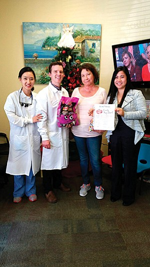 Dr. Caroline Hwang, left, and Dr. Peter March of Gentle Dental, Oceanside Resident Rose Papale, and practice manager Aileen Lao were part of a 2016 Halloween candy buy-back program. Photo courtesy of Gentle Dental