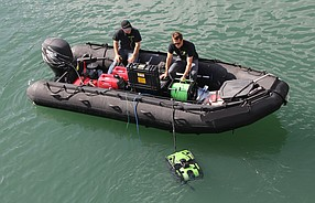 Technicians in a small boat put a SeaBotix unit through its paces. The robot swims at the end of a long tether - Photo courtesy of Teledyne SeaBotix
