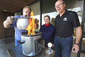 Tom Lillestol, left, holds a pot of water being heated by a wood stove Hi-Z Technology Inc. has outfitted with a thermoelectric generator. The U.S. EPA hopes the device will improve lives in India. Looking on are CFO and acting CEO Jill Elsner, center, and Vice President Fred Leavitt.