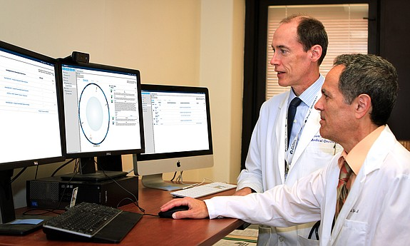 VA oncologists Michael Kelley (left) and Neil Spector review a Watson for Genomics DNA analysis report. Photo courtesy of IBM.