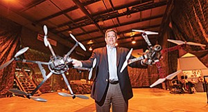 Rod Weiss, Coleman University's director of development, holds two aircraft at the university's Hornet's Nest, a 1980s industrial building converted to drone testing ground.