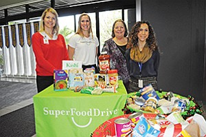 Megan Spurling, Sharp HealthCare, left; Cindy Knapp, SuperFood Drive; Jillian Barber, Sharp HealthCare and Liz Outlaw, Sharp HealthCare during a holiday food drive that promoted healthy food donations.  Photo courtesy of SuperFood Drive