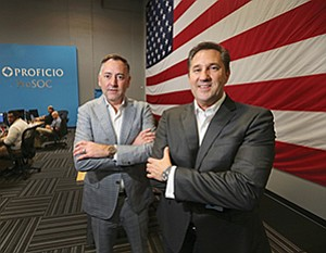 Proficio board Chairman Tim McElwee, left, and CEO Brad Taylor stand out of the way at the company's security operations center in Carlsbad. Out of view to the left are row upon row of cybersecurity analysts and responders.