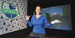 Street Swings CEO Jenn Harris stands in front of a high-tech golf simulator which uses infrared technology and two high-speed cameras to determine how and where a shot would travel on a particular golf course. Harris' company is unusual for the sector in that its simulator is mobile.