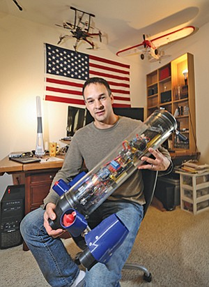 Phillip Rhyner shows off a toy submarine he built. He operates the toy in his apartment complex swimming pool. The engineer has yet to build his three robot subs for the XPrize competition. Those machines will be much more rugged and able to withstand pressures at depth.