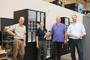 The engineering design team at SupplyPro Inc. and the company's CEO stand by the new inventory control system. From left, Scott Sansom, Stephanie Nims, CEO Floyd Miller and Scott Wessels.