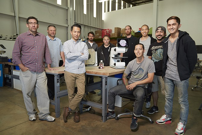 Building a novel microscope is a team effort at Echo Laboratories Inc. From left, Gabriel Esterman, Andy Bound, CEO Eugene Cho, Dorian Raymer, Jeremy Rohr, Adam Rusch, Anthony Beatty (sitting), Dave Shu, Nick Stavroulakis and Spencer Timme