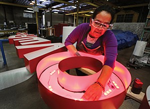 Maria Linan works on a sign at Federal Heath. The company has five manufacturing plants, all in the U.S., including a 42,000-square-foot Oceanside plant.