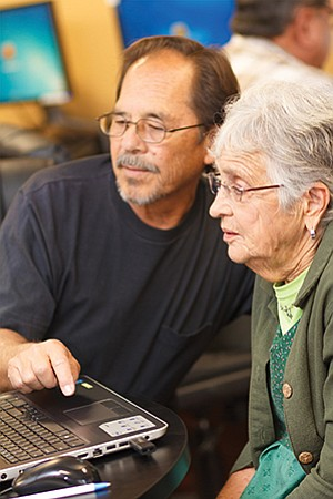 A Jewish Family Service of San Diego volunteer helps a senior navigate a computer, made possible by a grant from the Neighborhood Reinvestment Program. Photo courtesy of the Jewish Family Service of San Diego
