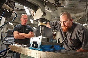 Greg Horan, left, supervises Jeremy Norman as he works on a milling machine in the Hunter Industries machine shop.